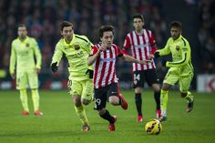 Lionel Messi of FC Barcelona duels for the ball with Unai Lopez of Athletic Club during the La Liga match between Athletic Club and FC Barcelona at San Mames Stadium on February 8, 2015 in Bilbao, Spain.