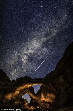 A meteor shooting over a rock arch