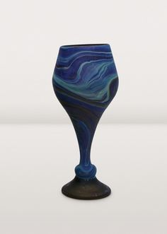 A colorful recycled glass goblet hand-blown by artisans of Hebron Glass & Ceramic Factory. In Phoenician glass blowing, artisans add substances to the molten glass, with the resulting reaction creating a range of colors. Working with this process takes an especially skilled hand, and is reserved for the true masters of the art. Each piece has its own unique blend of color and pattern. Buy a set for special occasions and wedding presents.