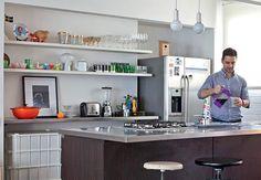Como a pia fica na bancada que divide a cozinha e a sala, o arquiteto Maurício Arruda aproveitou a parede para colocar prateleiras. Nelas, exibe utensílios, louças e peças de decoração, como uma fotografia emoldurada
