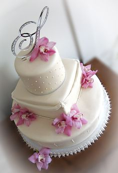 Ivory fondant, pearl details, silver ribbon, and rose orchids. I just LOVE this cake! It's my 4th wedding cake and I have to say, I've discovered that I just adore doing wedding cakes! Sooo much easier and less stressful than some of the other cakes I've done. The whole cake is covered in pearl spray and disco dust which sadly... you can't really see in the photo. But it really shimmered.