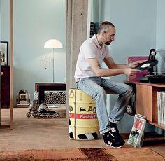 O designer de interiores Sandro Brasil usa tambor de óleo da Fórmula 1 como banqueta para mexer em sua coleção de vinil