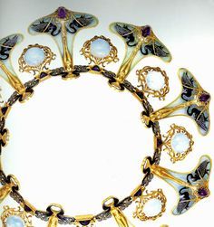 """""""Lalique designed one of his most famous and incredible necklace for the Parisian exposition.  Handcrafted in gold with nine nude female figurines standing on amethyst stones with black swans on each side of her feet, in between the figures are round opals all suspended from an ornately curved enameled neck ring."""""""