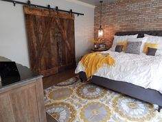 Basement bedroom with brick walls and large barn-like door - Decoist