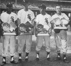 1960. Minnie Minoso, Jim Landis, Luis Aparicio, and Nellie Fox show off their Gold Glove awards.