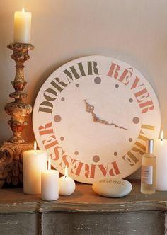Hologe en bois peinte au pochoir des mots lire, rêver, paresser et dormir.
