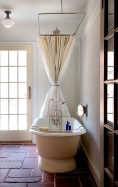 I have been thinking of adding a shower curtain system overhead to our claw foot tub, but hate the way it would take away from the whole look of the bathroom, but here is an idea as to what to do with the curtain when not in use. Hmmm.