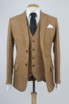 "Custom three piece suit features Herringbone pattern Brown 100% soft wool tweed Two buttons down the front Five buttons on vest Rear adjustable strap Flat front pants 6"" differential on pants"