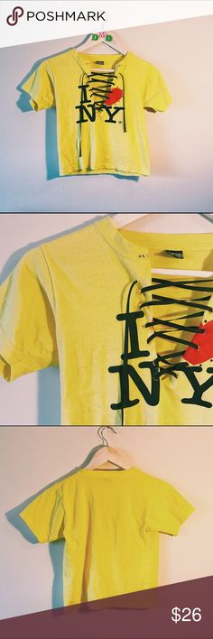 """Custom laced up bright yellow """"I ❤️ NY"""" crop top Purchased in NYC this was originally a child's shirt. it does as enough it's a crop top. cut it to have a v-neck and is laced with black string (no trim). shirt is some what  stretchy, gives excellent cleavage. so cute and so bright. in great shape. size small.   BUNDLE➕SAVE ‼️ buy 2+ items and receive AT LEAST 20% OFF ‼️ --- #yellow #iloveny #nyc #love #croptop #lacedup #bright #vneck #lowcut #busty #cleavage #sexy revamp'D Tops Crop Tops"""