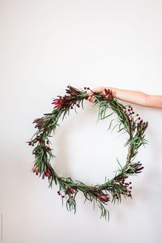 Woman Holding A DIY Christmas Wreath Download this high-resolution stock photo by Treasures & Travels from Stocksy United.