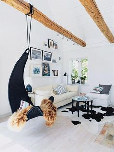 Airy living room with black wicker hanging chair and cowhide rug
