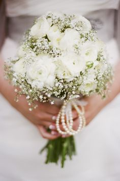 Bride bouquet carrying ranunculuses and baby's breath. Photo by jHenderson Photography.