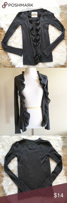 """Abercrombie kids charcoal ruffle cardigan ❤️ Ruffled collar, Abercrombie logo on the left bust ❤️Approx. Measurements, laying flat: Sleeve length 21"""" Bust  14"""" across chest Waist 14"""" Total length  22"""" shoulder to bottom hem  ❤️All measurements approximate, may vary depending on stretch of the fabric & person measuring. All used items may have loose threads which are not indicative of overall condition.Bundle your likes & I will send you a private offer abercrombie kids Shirts & Tops Sweaters"""