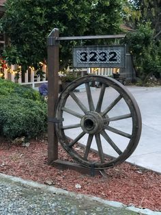 Wagon wheel address yard decoration Old wagon wheel turned yard decoration and address sign. Wagon wheel bought in Genoa, NV. Post and number board made by my husband, Mark Cardoza. Garden Yard Ideas, Backyard Projects, Outdoor Projects, Barn Wood Projects, Wagon Wheel Garden, Wagon Wheel Decor, Old Wagons, Front Yard Landscaping, Rustic Landscaping
