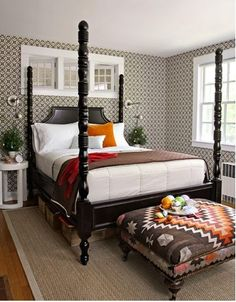 master bedroom with wallpaper on the walls, white bedding, and one southwest piece