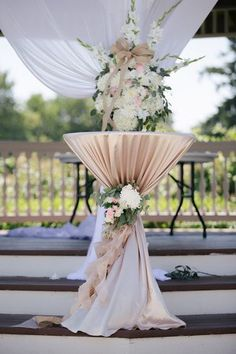 A high-top table cloaked in champagne ruffled linens and embellished with blush and ivory blooms {Clint Bargen Photography}