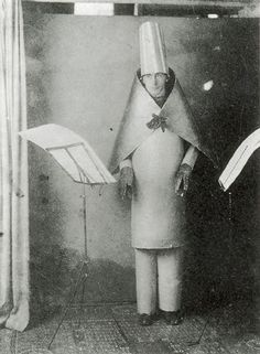 "This fine example of 'oddness in action' is this photo of a guy named Hugo Ball elaborately reciting a poem called Karawane. Hugo Ball, Hans Arp, Tristan Tzara und Marcel Janco were the founders of the famous Cabaret Voltaire in Zurich (Switzerland) which is known to be ""the cradle of dadaism"". Dadaism was a cultural movement that involved visual arts, literature, poetry, theatre and graphic design."