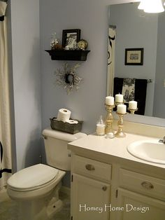 Bathroom Decor - I like the way the smaller shelf is above the toilet with the rolls on the top.  May have to do this upstairs!