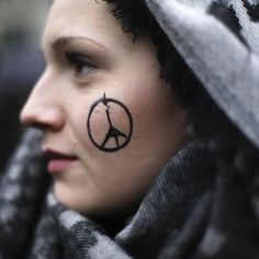 As the frenzied chaos and shock from the terror attacks in Paris settled into a sprawling criminal investigation police said they were hunting for an eighth attacker who might have escaped during the assault which killed 129 people and injured about 350 others. In this photograph by Markus Schreiber of @ap.images a woman shows a peace sign combined with the Eiffel Tower painted on her face as she arrives for a minute of silence for the victims of Friday's attacks in Paris in front of the…