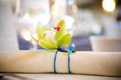 Handmade napkin rings accessorized with green orchids