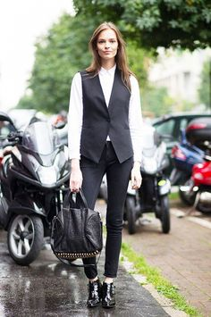 Sleek black vest, white oxford, and ankle boots.