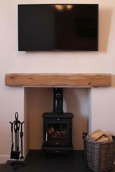 Wood burning stove with oak below a wall mounted flat screen smart TV