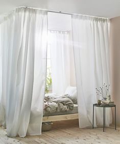 Want to know how to make a canopy bed? IKEA has all the products you need to set up this white curtain around a pine bed frame using our VIDGA track system including VIDGA corner piece single track.