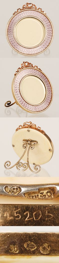 A Faberge gold and guilloche enamel frame, Moscow, circa 1896-1908. Of circular form, the surface decorated in translucent mauve enamel over a radiating engine-turned ground, between thin bands of opaque white enamel, the frame surmounted by an undulating rose gold bowknot; ivory back and gilded silver strut.