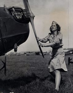 Pvt. Doris Elkington, a member of Michigan Wing 63 of the Civil Air Patrol, turns the propeller of her airplane before taking off on her tour of duty, 1943