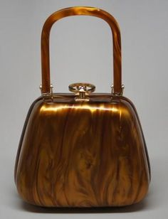 "Sold on Ebay as ""VINTAGE WALBORG BAKELITE HANDBAG"".  Tagged Waldorf, Hong Kong.    I believe this is Lucite, as I've found nearly identically styled bags for sale online that were made in Hong Kong under the name ""Stylecraft""."