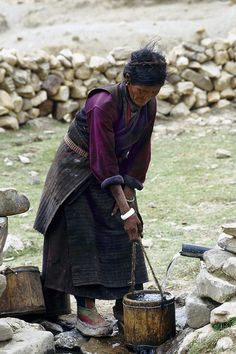 A Khampa woman fills her water buckets at a small water outlet, the village's only water supply, in a tiny village within the Mt. Everest Nature Preserve, Tibet.