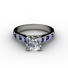 Round Brilliant Cut Blue Sapphire Engagement Ring.  Elegant and unique, this diamond engagement ring showcases sixteen round brilliant cut diamonds and blue sapphires that are channel-set in gold or platinum to accent your center diamond.  Sale Price (45% OFF): US $ 1,953.00.  https://www.nataliediamonds.com/product/round-brilliant-cut-blue-sapphire-engagement-ring/  #NatalieDiamonds #engagementrings #diamonds