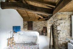 Una de las habitaciones - AD España, © Carlos Onetti En esta estancia se dejó a la vista la pared de piedra original. Foto Carlos Onetti