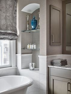 arched bathroom niche with glass shelves & mosaic tile