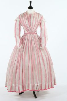 A pink and white striped muslin summer gown, circa 1864. the collar and mancherons trimmed with cotton torchon lace, fanned panels of tight pleats to bodice front and back, integral camisole, watch pocket to waist