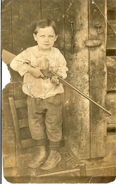 Harts Creek, West Virginia child with rifle, 1916-1920.--Polite kid. He's standing on a chair so he won't blow your kneecaps off.