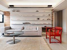 Graues Sofa und roter Armlehnstuhl aus Holz vor Designer Einbauregal