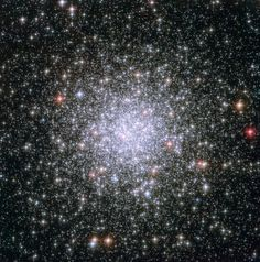 A hazy blob of stars punctuated by close golden bursts
