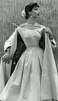 1960, hourglass, long sleeves, long fabric draping off both shoulders, shoulders pretty much fully exposed