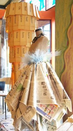 Mannequin newspaper skirt and old school flash card chandelier!  Shabby creativity !!