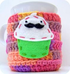 """Mustache Cupcake coffee mug cozy handmade by KnotworkShop, $15.00 ... Diane from KnotworkShop says that she created this cozy because it made her laugh.  As she explains:  """"Cupcakes are yummy. Mustaches are silly. A cupcake with a mustache is downright hilarity.""""  You go, girl!"""
