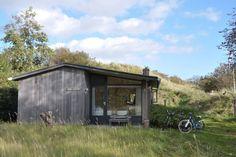 """Het karakteristieke vakantiehuis """"Oude Wal"""" bevindt zich in """"Klein Zwitserland"""", een rustig duinpark op het eiland Schiermonnikoog. Comfortabel, eigen duinopgang met prachtig uitzicht en een paar minuten lopen van het Westerstrand. Het karakteristieke vakantiehuis """"Oude Wal"""" bevindt zich in """"Klein Zwitserland"""", een rustig duinpark ten westen van het dorp Schiermonnikoog. In het park is een privé-tennisbaan en het brede Westerstrand is een paar minuten lopen.  Prefab Cottages, Barn House Plans, Tiny House, Bungalows, Holland, The Good Place, Shed, Places To Visit, Outdoor Structures"""