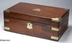 WB167: Figured rosewood writing box with brass corners and straps escutcheon and plate opening to an embossed leather (replacement) writing surface and compartments for writing implements and paper, and having two secret drawers concealed behind a sprung panel. The box has two hand blown replacement reproduction inkwells. Circa 1840 Enlarge Picture