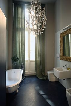 Moody bathroom with tall French doors dressed in sage green curtains alongside taupe walls over ...