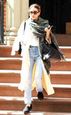 Ashley Olsen wears an oversized coat, plaid scarf, and light washed blue mom jeans with all black accessories.