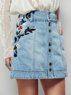 look annee 1980 mini jupe en denim bleu clair avec des broderies de fleurs autour l'une des poches