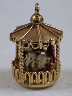 This 14k Yellow gold Wind-Up Motion Carousel Charm is in good condition. Features red, yellow, green and white horses..