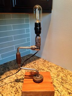 This industrial lamp would look great in your living room or office. Made from a hand brace, the Edison bulb is included and is attached to a solid wood base. The lamp is approximately 15 tall with a 6 cord.