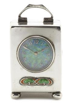 Liberty & Co A 'Cymric' Silver and Enamel Carriage Clock, 1904 the circular face with mottled green and blue enamel, decorated below with twin foliate motifs in orange and green enamel, raised off four bun feet 8cm high, stamped 'L' with Birmingham hallmarks, stamped '5503' to base