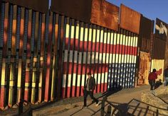 """People pass graffiti along the border structure in Tijuana, Mexico, Wednesday, January 25, 2017. President Donald Trump moved aggressively during his first week in office by signing executive actions to jumpstart construction of his promised U.S.-Mexico border wall and cut federal grants for immigrant-protecting """"sanctuary cities.""""   Photo credit: AP Photo / Julie Watson"""